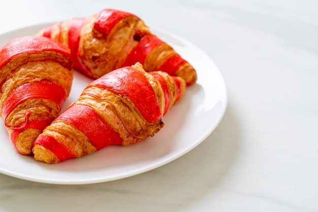 Verse croissant met aardbeienjam saus op plaat