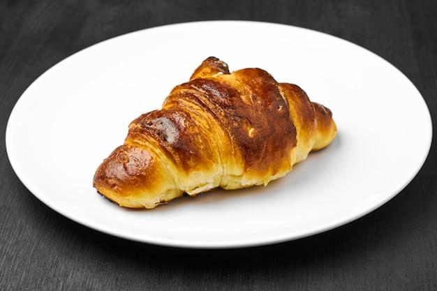 Verse croissant met een bruine korst op een witte plaat op een zwarte tafel.