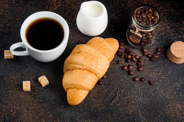Verse croissant met een mok ik zwarte koffie en koffiebonen op donkere betonnen ondergrond. het concept van warme dranken, verkwikkend ontbijt.