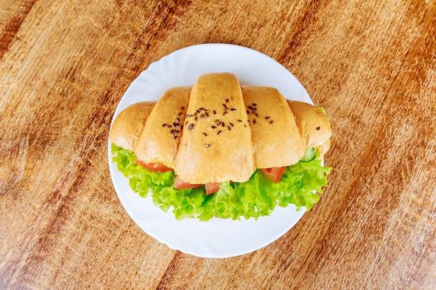 Verse croissant met ham en sla op een houten tafel in een café. groentecroissant