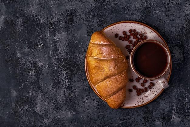 Verse croissant op donkere ondergrond met koffie