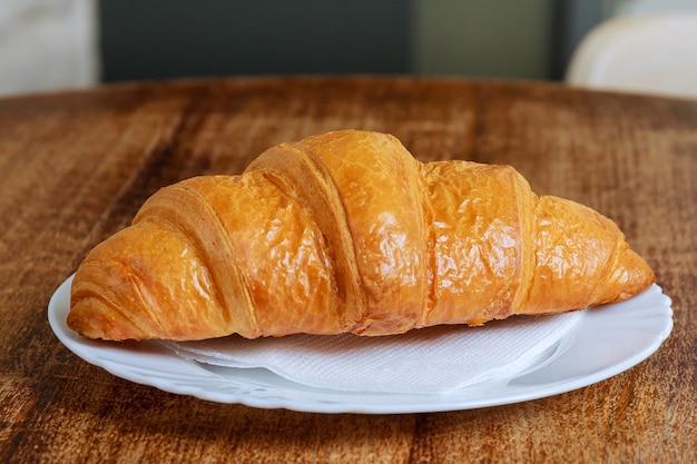 Verse croissant op een witte plaat op een houten tafel in een coffeeshop.
