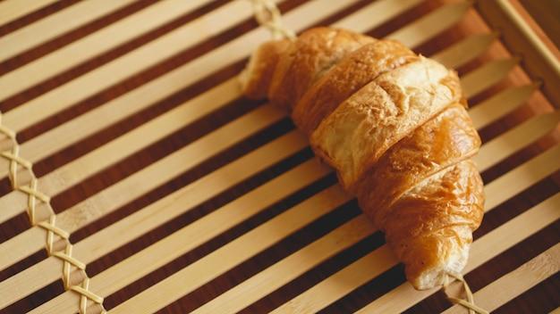 Verse croissant op rustieke houten achtergrond. selectieve focus, horizontaal.