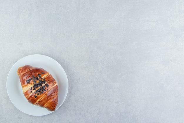 Verse croissant versierd met drop chocolade op witte plaat.