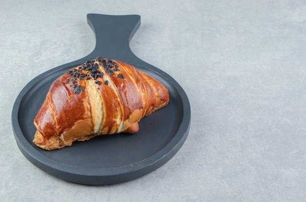 Verse croissant versierd met drop chocolade op zwart bord.