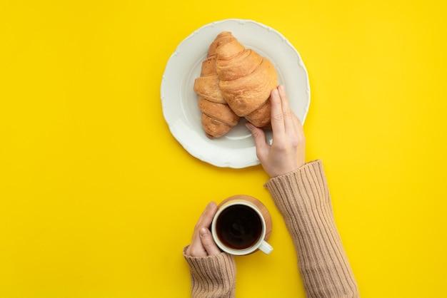 Verse croissants en warme koffie, een vrouwelijke hand met een kopje.