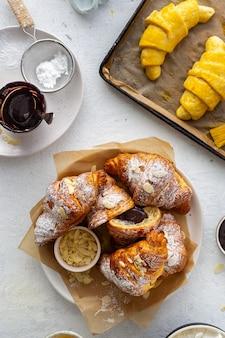 Verse croissants met amandelvlokken en poedersuiker bovenaanzicht