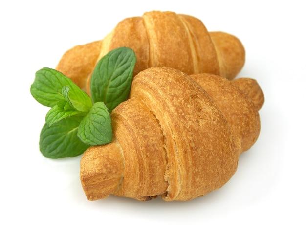 Verse croissants met munt op een witte achtergrond