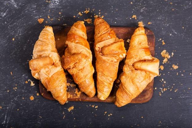 Verse croissants op een houten bord, bovenaanzicht