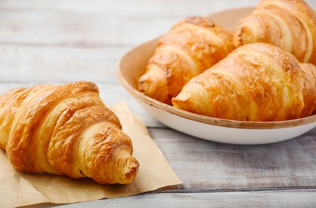 Verse croissants op houten tafel.