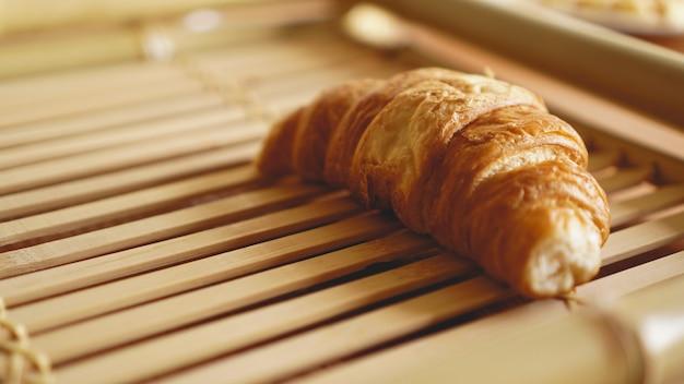 Verse croissants op rustieke houten achtergrond. selectieve focus, horizontaal.