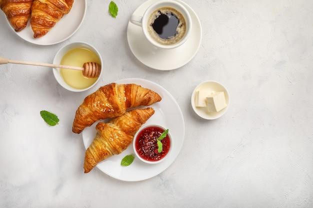 Verse croissants, zwarte koffie en jam op wit.