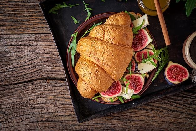 Verse croissantsandwich met brie-kaasarugula en fig. heerlijk ontbijt.
