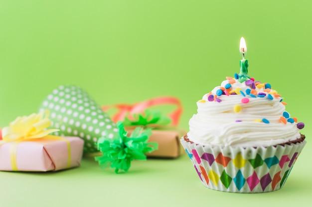 Verse cupcake met verlichte kaars op groen oppervlak