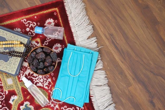 Verse dadelfruit in een kom gebed rozenkrans handdesinfecterend middel en masker op vloer