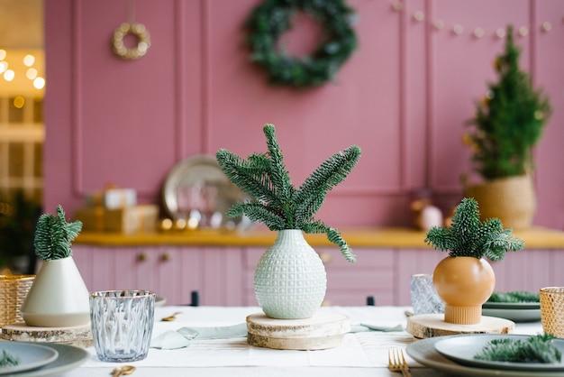 Verse dennentakken of dennen in een keramische vaas, een vaas op de keukentafel in versierd voor kerstmis