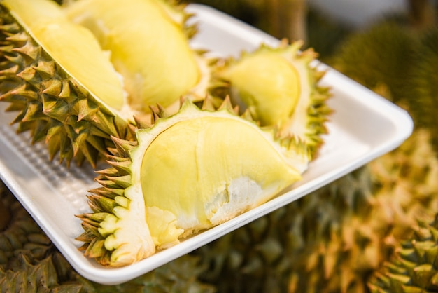 Verse die durian op dienblad en rijp durian fruit op achtergrond voor verkoop in de markt wordt gepeld