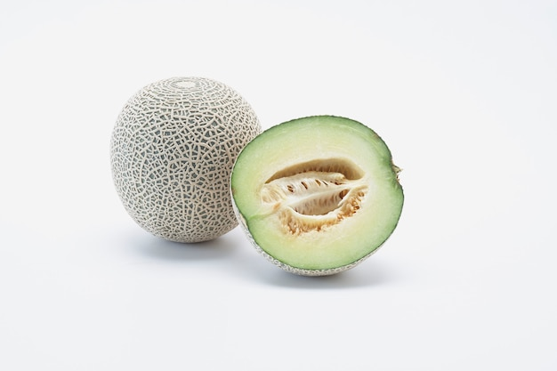 Verse die hami-kantaloepmeloen met plakken op witte achtergrond worden geïsoleerd.
