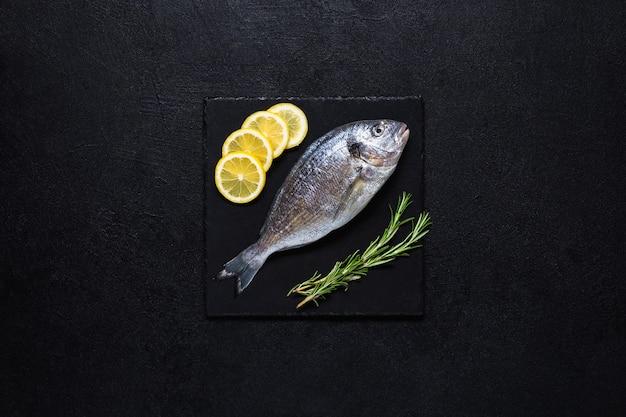 Verse dorado bereid om te koken op een zwarte stenen snijplank met citroen en rozemarijn op een zwarte achtergrond. bovenaanzicht.
