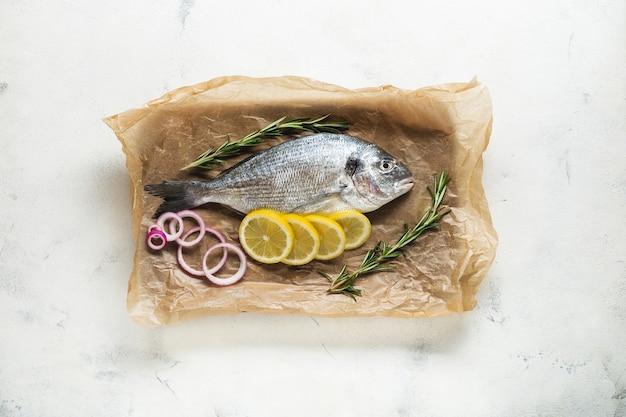 Verse dorado op een snijplank met citroen en kruiden bereid om te koken. bovenaanzicht.