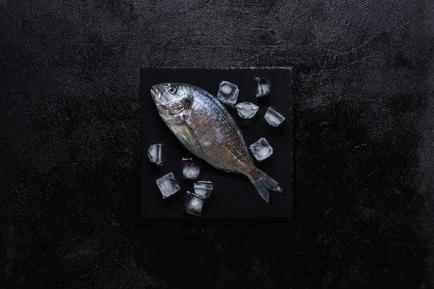 Verse dorado op een zwarte stenen snijplank met stukjes ijs. bovenaanzicht. zwarte achtergrond.