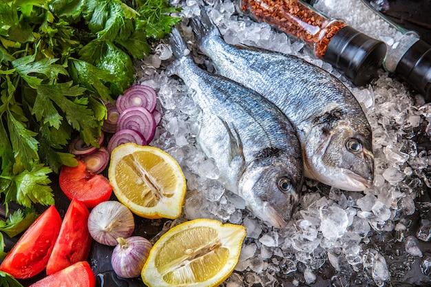 Verse dorado vis, met groenten, kruiden, citroen met stukjes ijs op een zwarte achtergrond