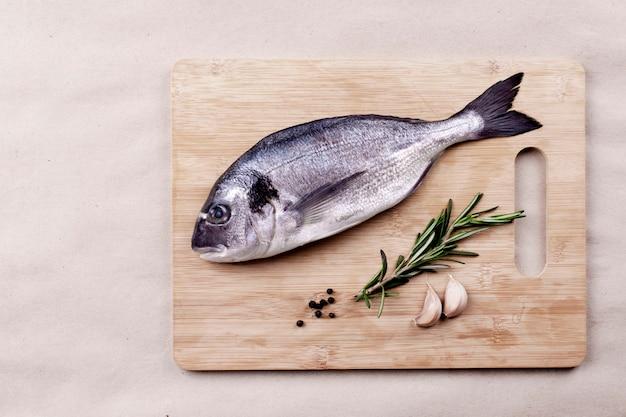 Verse dorado vis zeevruchten op houten plank of bord.