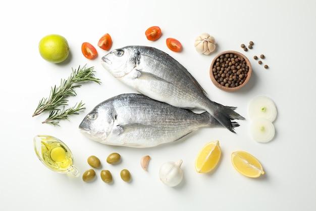 Verse dorado-vissen, kruiden en kokende ingrediënten op wit
