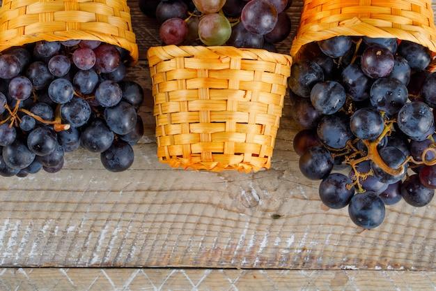 Verse druiven in rieten manden op houten achtergrond, close-up.