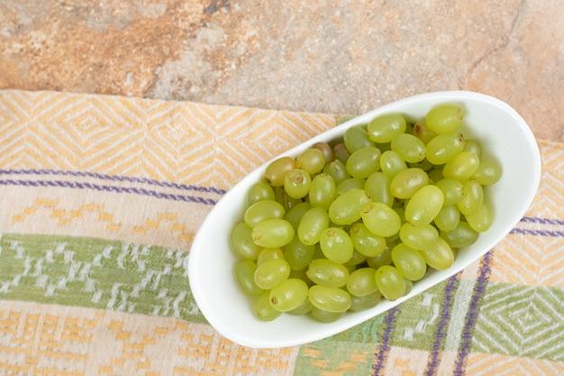 Verse druiven in witte kom op tafellaken.