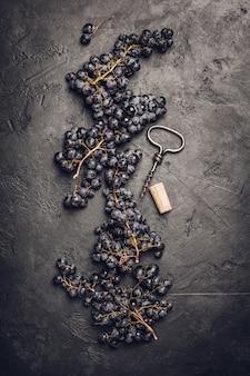 Verse druiven, kurk en kurketrekker op donkere achtergrond