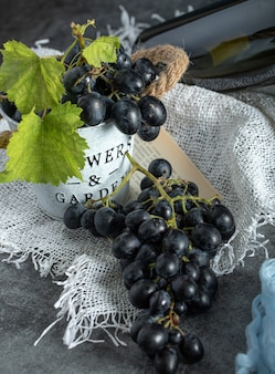 Verse druiven met bladeren in emmer op zak