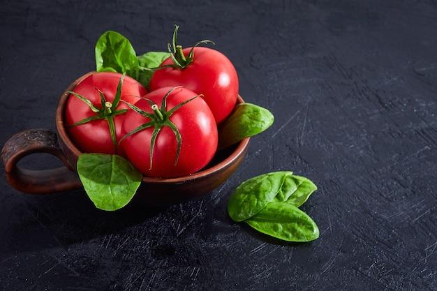Verse druiven tomaten met spinazie bladeren op zwarte stenen achtergrond. kruid, tomaten, kookconcept.