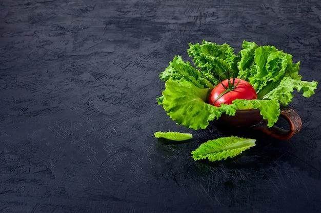 Verse druiventomaten met salade bladeren op zwarte steenachtergrond. veganistische groenten dieetvoeding. kruid, rode tomaten, kookconcept.