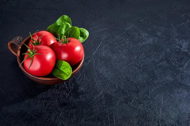 Verse druiventomaten met spinaziebladeren op zwarte steenachtergrond. veganistische groenten dieetvoeding. kruid, rode tomaten, kookconcept.