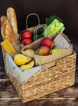 Verse eco biologische groenten, groenten en fruit, granen en pasta in een rieten mand. levering of schenking van ecologisch boerderijvoedselconcept