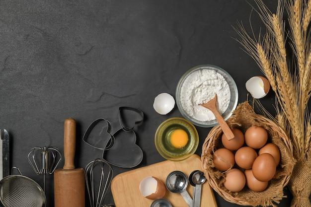 Verse eieren en cakemeel met keukengerei voor gebak op zwarte tafel,
