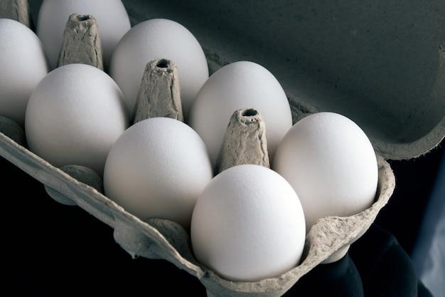 Verse eieren in de geopende doos op zwarte achtergrond