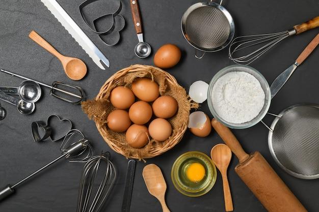 Verse eieren in de mand en keukengerei voor gebak op zwarte tafel