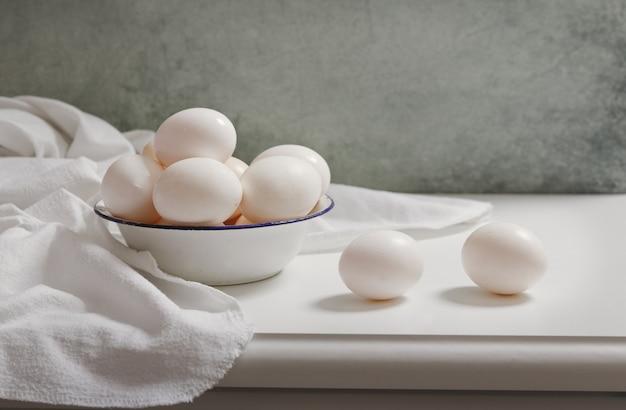 Verse eieren in een kom op houten tafel