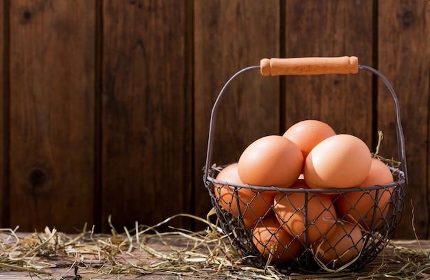 Verse eieren in een mand op houten tafel Premium Foto
