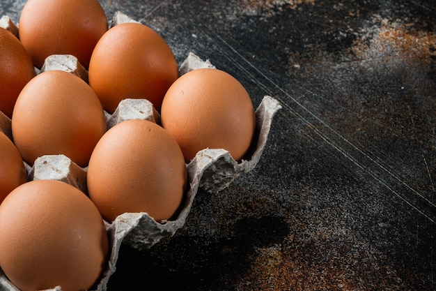 Verse eieren op papier eierdoos set, op oude donkere rustieke tafel, copyspace
