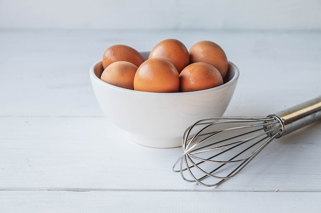 Verse eieren voor het koken op een witte houten tafel