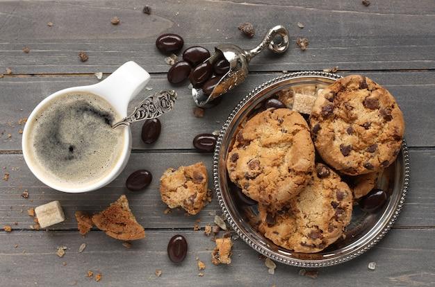 Verse eigengemaakte chocoladeschilferkoekjes met kop van espresso op oude houten achtergrond