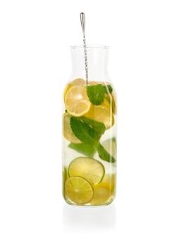 Verse eigengemaakte limonade met munt en staaflepel in bevroren geïsoleerde glasfles