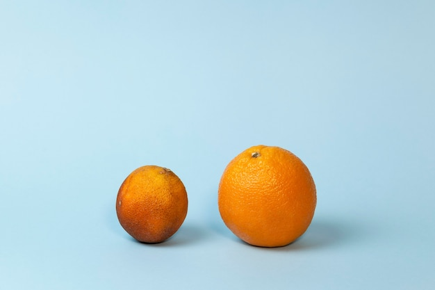 Verse en bedorven sinaasappelen op lichtblauw