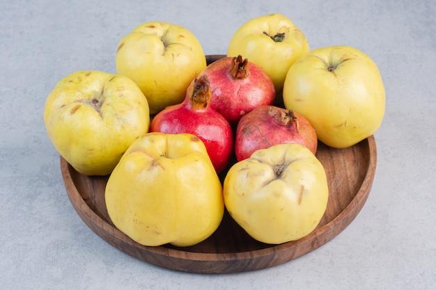 Verse en biologische appelkweepeer en granaatappel op een houten bord.