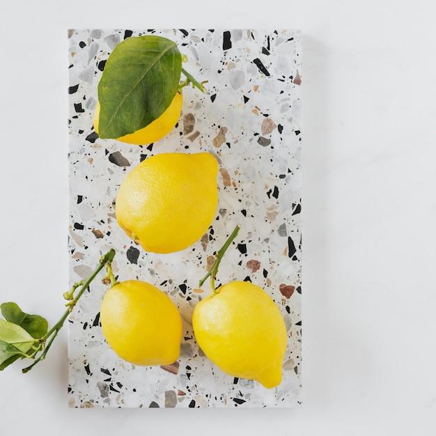 Verse en biologische citroenen op een marmeren snijplank flatlay