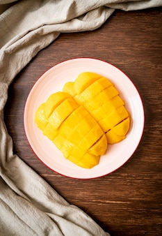 Verse en gouden mango die op plaat wordt gesneden