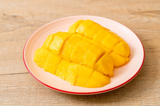 Verse en gouden mango gesneden op plaat